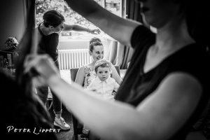 """Kind auf dem Schoß der Mutter während dem schminken """"herrichten"""" der Frauen vor einer Hochzeitsfeier"""